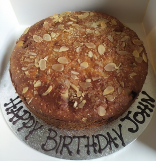Cherry and almond cake, message piped around the board