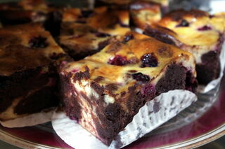 Deep slice of chocolate and blackberry cheesecake brownie