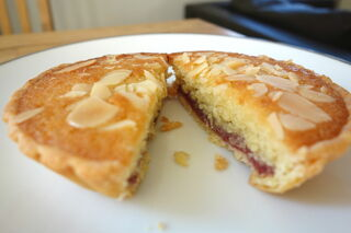 Individual bakewell tart sliced in half with flaked almonds on top