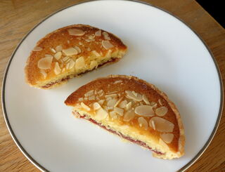 Plate with individual bakewell tart sliced in two