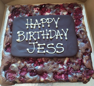 Whole tray of chocolate and raspberry cheesecake brownie, with a chocolate plaque with message
