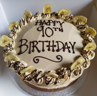 2-layer banana cake with toffee buttercream, birthday message piped on top