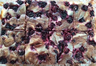 Most of a tray of chocolate and blackberry cheesecake brownie, sliced