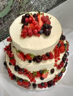 3-tier wedding cake iced all over, with fresh berries and cherries