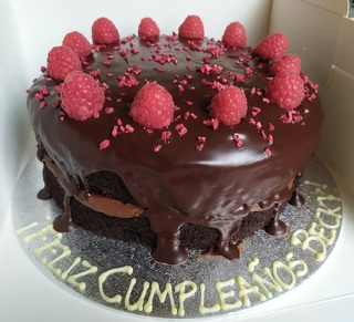 2-layer 8in chocolate and raspberry cake with dark chocolate ganache, message on the board