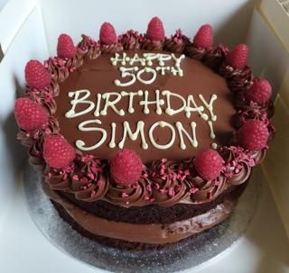2-layer dark chocolate and raspberry cake, birthday message piped on