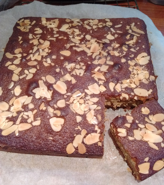 Square honey cake with slice removed, covered in flaked almonds