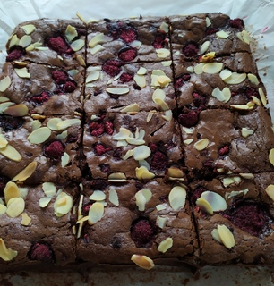 Whole tray of raspberry and almond brownie, sliced