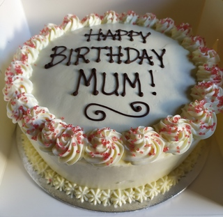 2-layer red velvet cake with cream cheese icing all around the sides, message piped on top
