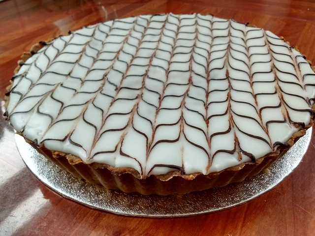 Whole gluten free bakewell tart with classic feathering design in icing