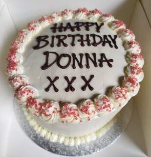 Red velvet cake iced around the sides with writing