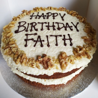 2-layer vegan carrot and coconut cake with walnuts, message piped on top