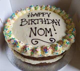 2-layer dairy-free nut-free carrot cake with rainbow sprinkles, birthday message piped on