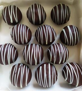 Box of dark chocolate cake bites with white chocolate drizzle