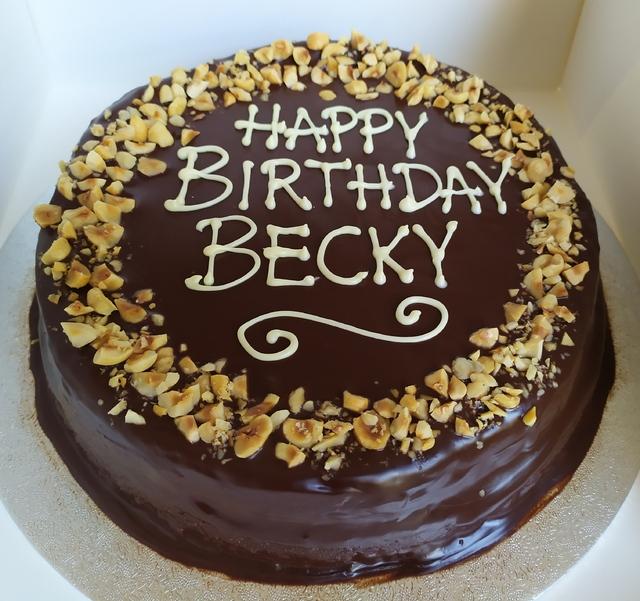 Chocolate and hazelnut cake with dark chocolate ganache, toasted hazelnuts, piped message
