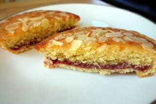 Individual bakewell tart sliced in half showing raspberry jam filling