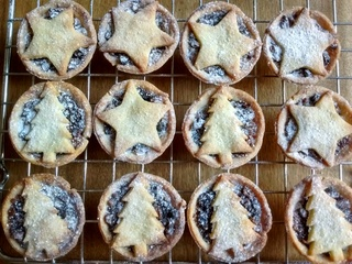 Selection of mince pies with christmas tree and star design lids, dusted with icing sugar