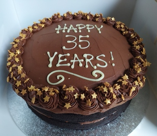 2-layer vegan chocolate cake with gold stars and message piped on top