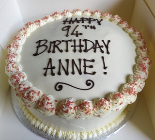 Red velvet cake iced around the sides with writing 9in