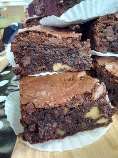 Pieces of chocolate fudge brownie looking squidgy, with walnuts peeping through
