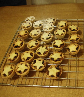 Tray of mince pies with star design lids on cooling rack